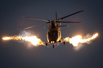 Poster Helicopter Military helicopter in flight firing off flare decoys at night.