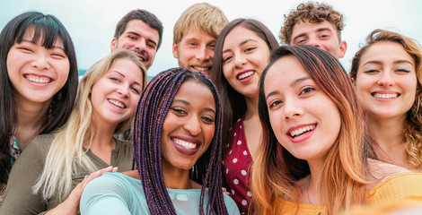 Young friends from diverse cultures and races taking photo making happy faces - Youth, millennial generation and friendship concept with students people having fun together - Focus on close-up girls