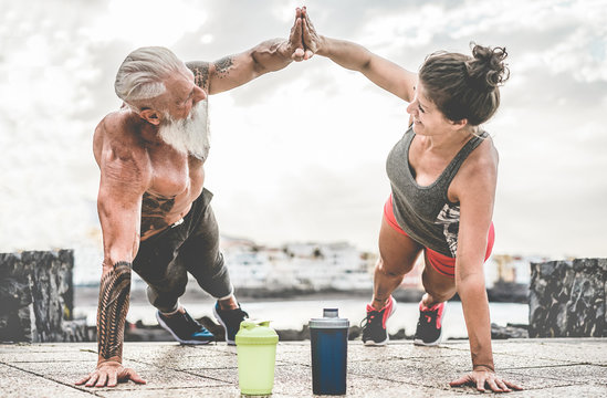 Couple of fitness athlete doing workout sessions outdoor - Happy trendy athlete people training outside - Bodybuilding, empowering and sport concept - Focus on hands