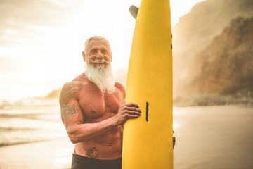 Tattooed senior surfer holding surf board on the beach at sunset - Happy old guy having fun doing extreme sport - Joyful elderly concept - Focus on his face