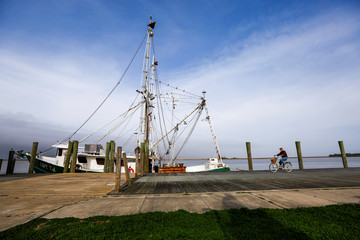 """A man bicycles past the shrimp boat """"Capt. T.J."""" owned by the 13 Mile Seafood company while it is docked in Apalachicola, Florida"""