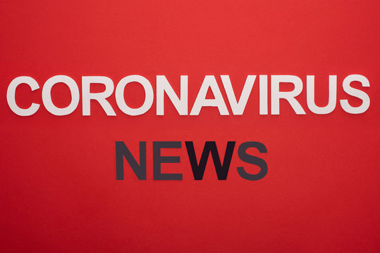 Top view of coronavirus news lettering isolated on red