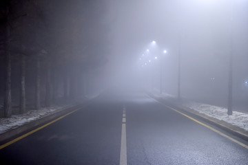 Fotomurales - Misty road at night. Empty night road with dense fog. Dangerous driving conditions.