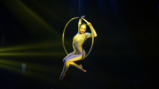 Flexible young woman make performance on aerial hoop, aerial circus show, yellow light. Flexible woman gymnast sits on hoop, black background