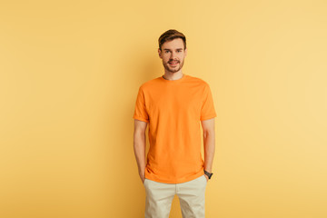 smiling young man in orange t-shirt standing with hands in pockets on yellow background Fotomurales