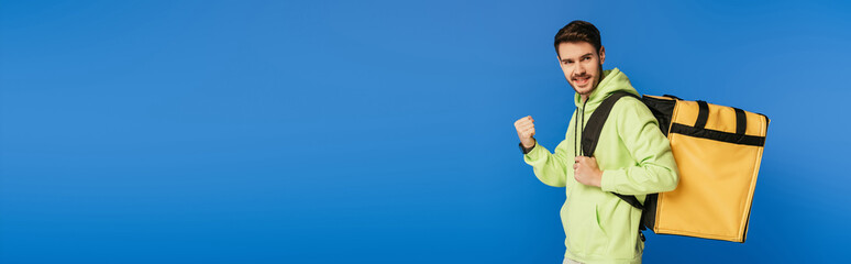 panoramic shot of happy delivery man showing winner gesture while carrying thermo backpack isolated on blue