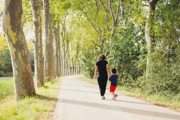 Promenade entre une mère et son fils le long du canal du midi, occitanie, france Wall mural
