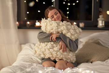 Fototapete - christmas, holiday and people concept - happy young woman with soft pillow in bed at home bedroom at night