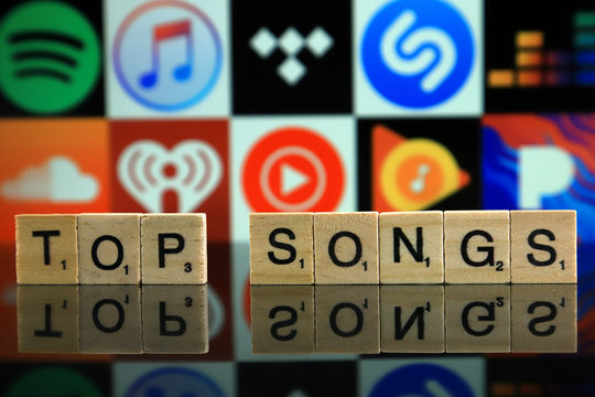 WROCLAW, POLAND - FEBRUARY 19, 2020: Words TOP SONGS made of wooden letters, and SPOTIFY, ITUNES, TIDAL, SHAZAM, DEEZER, SOUNDCLOUD, IHEART RADIO, YOUTUBE MUSIC, GOOGLE PLAY MUSIC, PANDORA logos.