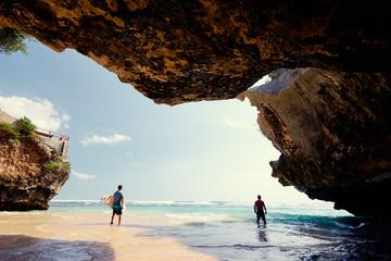 Hobby and vacation. Surfers with surfboard on beautiful beach with high rocks. Uluwatu spot, Bali island, Indonesia. Wall mural