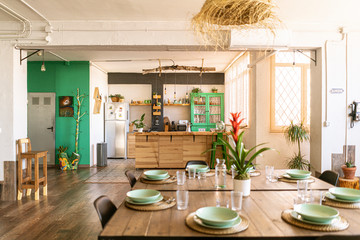Fototapeta Interior design / decoration. Spacious open kitchen and dining room in bright industrial loft, with table set ready for a nice meal. obraz