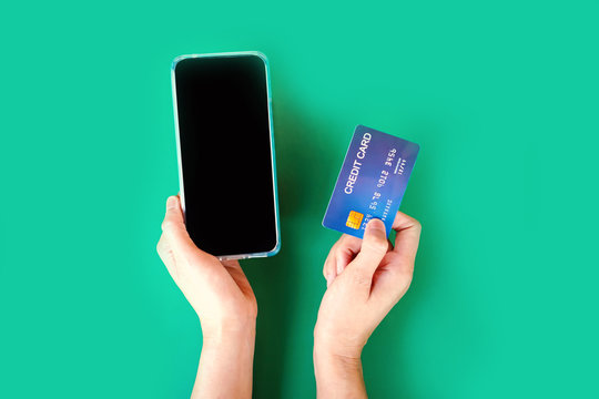 online shopping concept with woman hand holding smart phone and credit card top view on green background