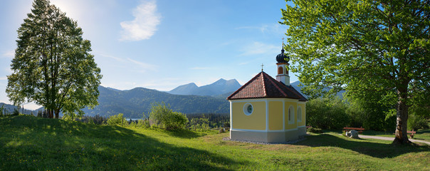 beautiful pilgrimage chapel at the hill, trees and mountain view, upper bavaria in may. Wall mural