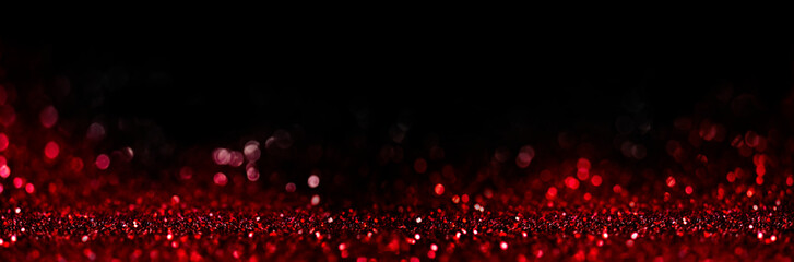 Abstract blur red glitter on black background. Card for Valentine's day, christmas and wedding celebration. Love bokeh sparkle confetti textured layout.