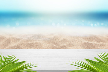 Wall Mural - White Wooden Desk Table Top with palm leaves frame design with Sea Sandy Beach ans Sunny bright sky background Summer concept