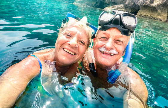 Happy retired couple with scuba mask taking selfie at tropical excursion - Boat trip snorkel experience in exotic scenarios - Elderly concept with active seniors traveling around world - Bright filter