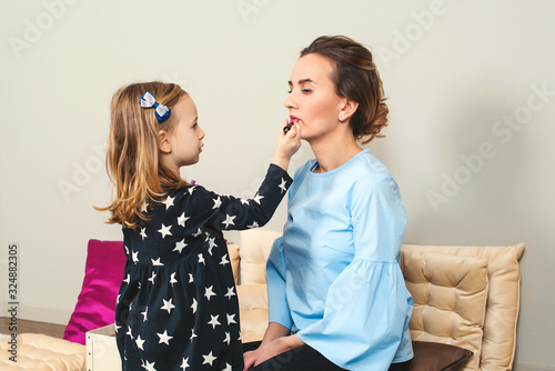 Happy loving family. Mother and daughter are doing makeup. Lovely mom and child having fun together. Mother's Day.