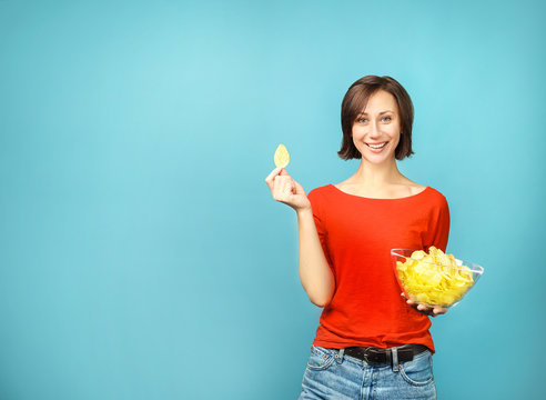 Beautiful woman holding chips on  blue background