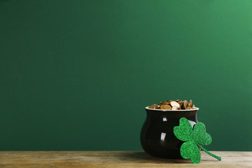 Pot of gold coins and clover on wooden table against green background, space for text. St. Patrick's Day celebration