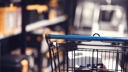 Supermarket aisle with shopping cart in blurred department store background.