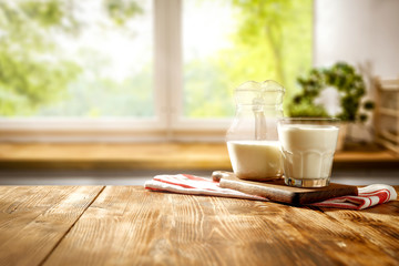 Wall Mural - Fresh cold milk on wooden table and kitchen interior.Spring sunny day and free space for your decoration.