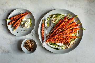 Overhead view of grilled carrots served with hazelnut dukkah, yogurt and carrot top oil on table