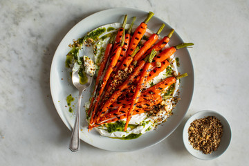 Overhead view of grilled carrots served with hazelnut dukkah, yogurt and carrot top oil on plate