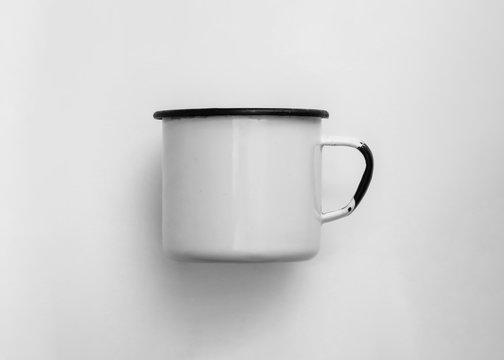 White blank enamel mug isolated on white background. Old worn enameled cup