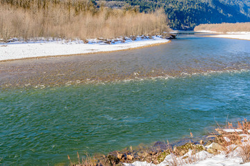 Wall Mural - Majestic mountain river in winter over snow mountains and blue sky in Vancouver, Canada.