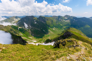great summer scenery of high mountain range. steep slopes with rocks, grass and spots of snow. clouds on the blue sky. explore fagaras ridge of romania travel concept