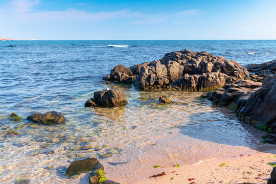 rocks on the sea beach in the morning. calm sunny weather. secluded place. fluffy clouds above the horizon.