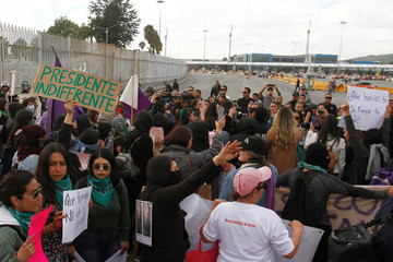 Police officers block women marching toward the Mexico-U.S. San Ysidro border crossing (foreground) during a protest against femicide and gender violence, in Tijuana