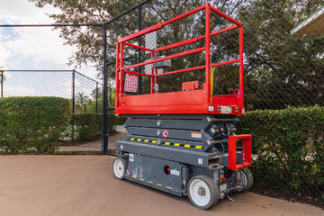 A aerial work platform also known as a hydraulic scissor lift, next to chain link fence on a tennis court