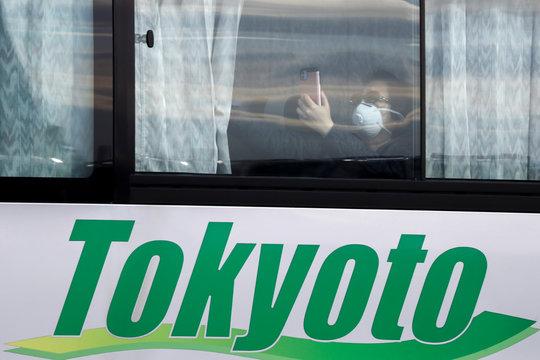 A passenger wearing a mask takes pictures as she leaves the coronavirus-hit cruise ship Diamond Princess at Daikoku Pier Cruise Terminal in Yokohama