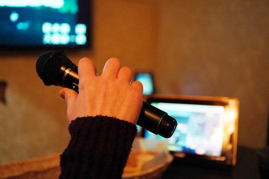日本人が大好きな趣味のカラオケ カラオケルームで歌う手とマイク