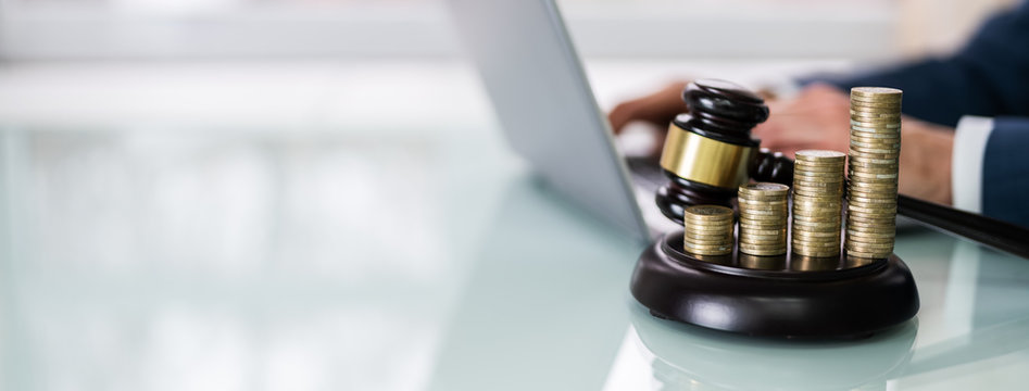 Judge Using Laptop Near Gavel And Stacked Coins