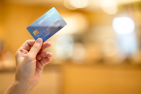 business shopping merchant ideas concept Close up of woman hand holding credit card for shopping with abstract blur mall background