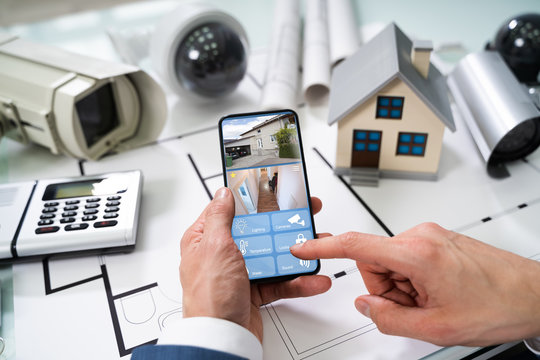 Person Hand Using Home Security System On Mobilephone