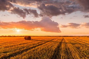 Printed kitchen splashbacks Culture Scene of sunset on the field with haystacks in Autumn season. Rural landscape with cloudy sky background. Golden harvest of wheat.