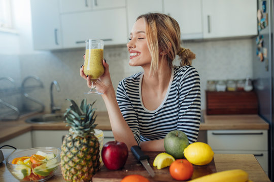 Happy smiling  healthy woman drinking smoothie
