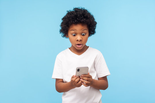 Astonished cute little boy with curly hair reading message on smartphone and expressing amazement shock, surprised by mobile application, using cellphone. studio shot isolated on blue background