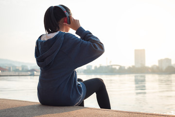 Young woman is relaxing and listening to music in the city after run.