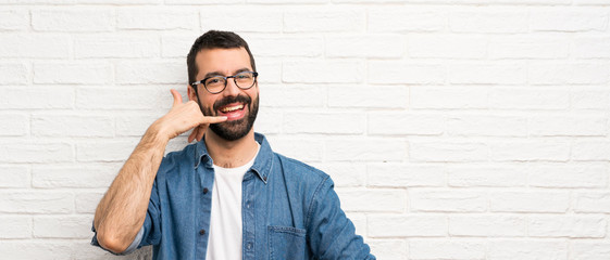 Handsome man with beard over white brick wall making phone gesture. Call me back sign