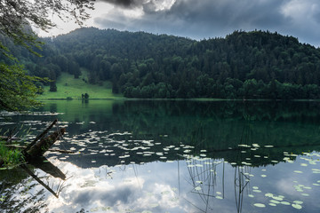 Reflecting bavarian lake with dramatic clouds