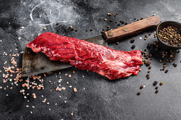 Poster de jardin Steakhouse Raw skirt, machete steak on a meat cleaver. Black background. Top view