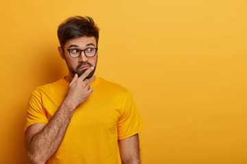 Puzzled thoughtful young man holds chin and looks away, fascinated by unexpected relevation, wonders to see something amazing, wears yellow t shirt and spectacles, poses indoor, blank space aside