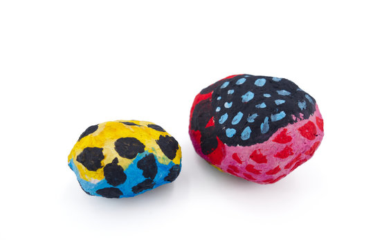 Round hand-crafted papier mache objects, painted in different colors and abstract patterns on a white background. Representing the creative process and creativity. Possible backdrop for presentations.