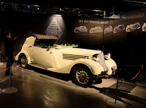 """A woman takes a picture of the rare 1935 Renault Nervasport model ACN-1 car during the """"Garage"""" exhibition, in the Riga Motor Museum"""