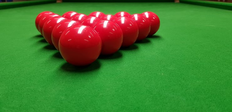 snooker balls and cue on a green table