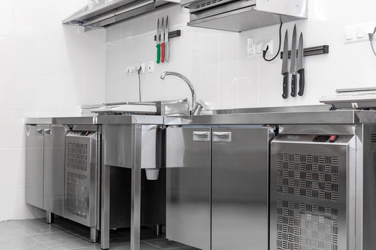 Design of the working area of the commercial cafe kitchen with stainless steel equipments, hot shop, food industry.